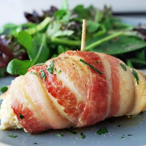 close up of a bacon-wrapped chicken breast sprinkled with fresh parsley on a plate with greens