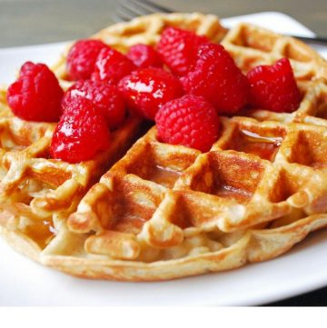 Belgian protein waffle on a plate with raspberries and syrup