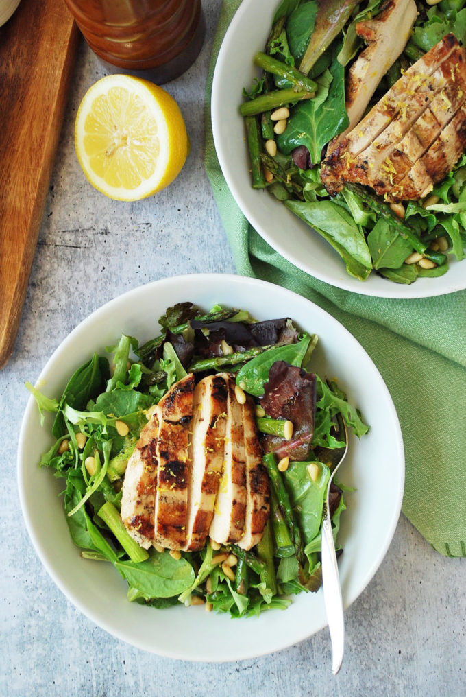 Two bowls of grilled chicken salad with roasted asparagus and pine nuts