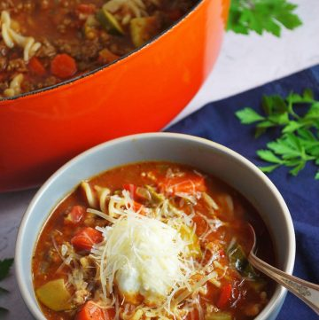 bowl of lasagna soup with pot of soup in the background and fresh herbs