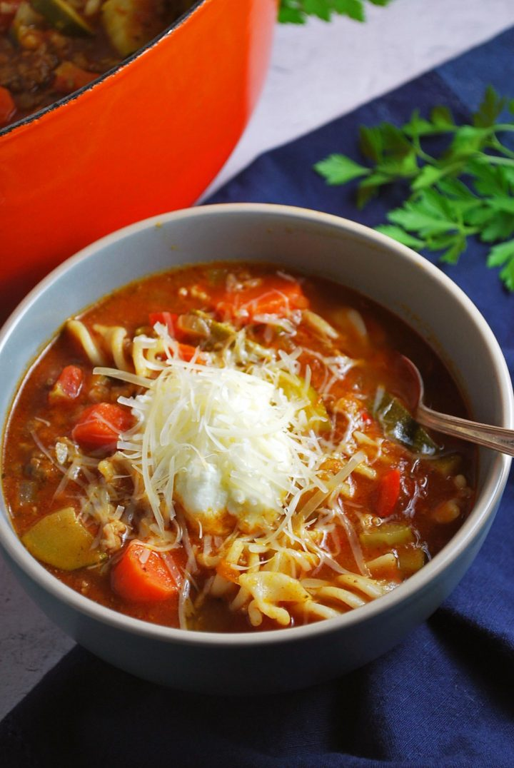 close up of bowl of lasagna soup topped with cheese with blue napkin and fresh herbs in the background
