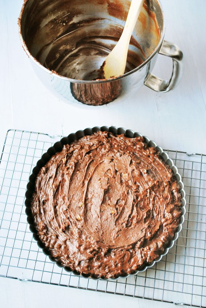 brownie batter in tart pan ready to bake with empty bowl and spoon