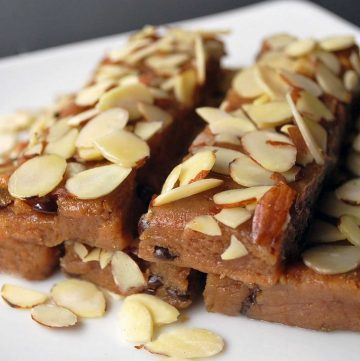 close up photo of homemade protein bars stacked on a plate topped with sliced almonds