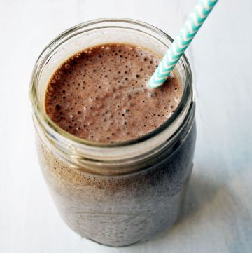 close up photo of blueberry chocolate protein shake with straw in a mason jar