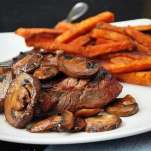 grilled steak on a plate topped with sauteed mushrooms with a side of sweet potato fries