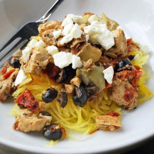 chicken with sun-dried tomatoes, olives, feta cheese and artichokes over a bed of cooked spaghetti squash in a bowl with a fork