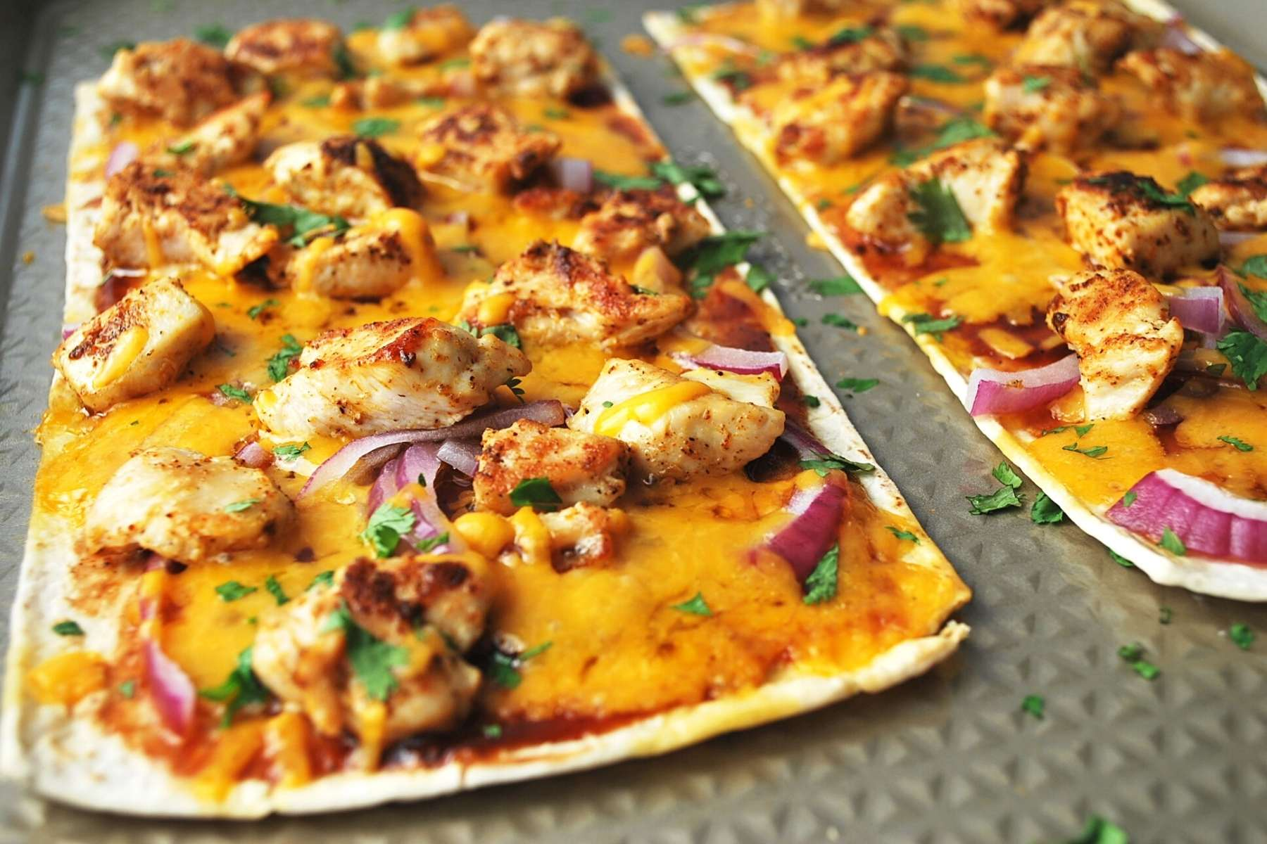 BBQ chicken flatbreads fresh from the oven on a baking sheet