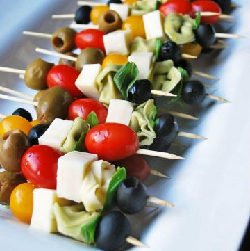 platter of skewers made with tortellini pasta, tomatoes, olives, fresh basil and cheese