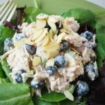 chicken salad with blueberries and almonds on a bed of greens in a bowl