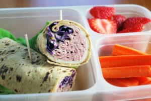 Meal prep container with a Reuben wrap sliced in half, carrots and fresh sliced strawberries
