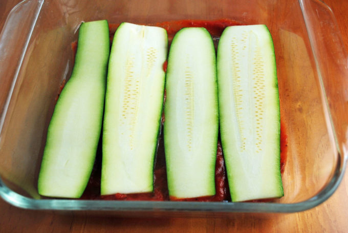 Fresh sliced zucchini on top of marinara sauce in a baking dish