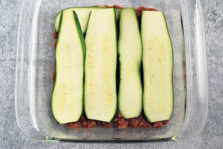 sliced zucchini over a layer of sauce in baking dish
