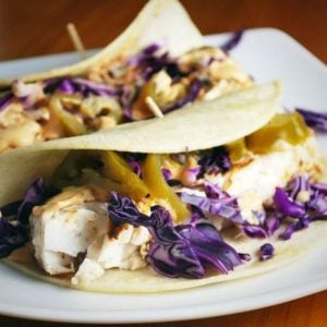 two fish tacos on a plate with purple cabbage and jalapenos