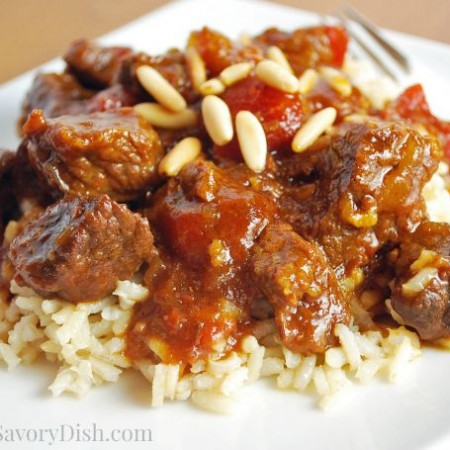 Marrakesh beef over rice topped with pine nuts on a plate with a fork