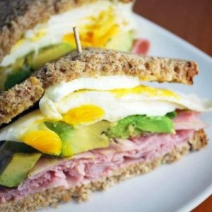 close up photo of a ham, egg, and avocado sandwich sliced in half on a white plate