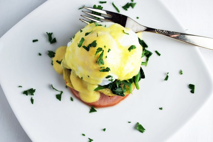 overhead shot of eggs benedict on a plate with fork