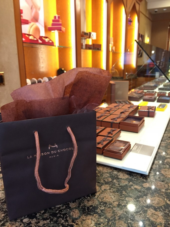 A brown bag with M Chocolates written on the front with chocolates in the background