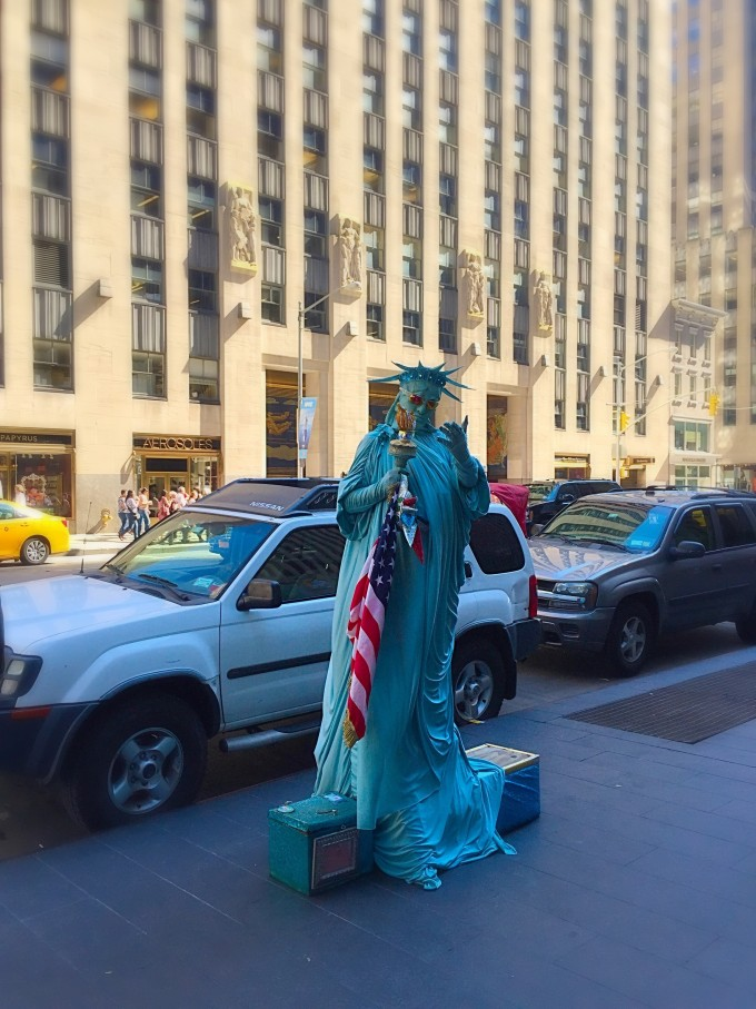 A car parked on a city street with a woman dressed up as the Statue of Liberty in front