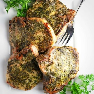 platter of herb-rubbed pork chops with a fresh herb garnish