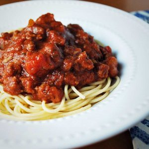 spaghetti sauce piled on top of noodles in a white bowl