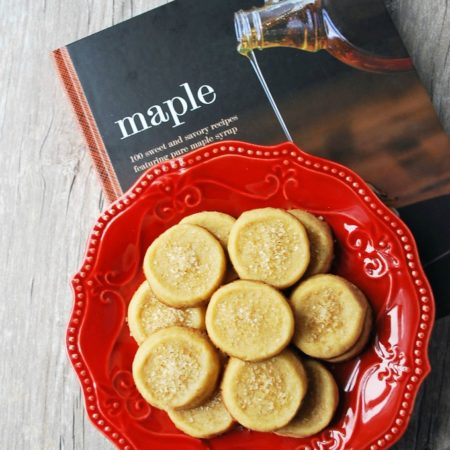 Maple cookies on a red plate with a cookbook underneath