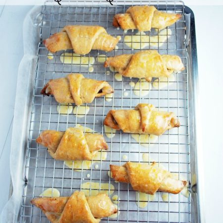 Croissants on a baking sheet drizzled with glaze