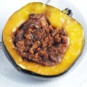 close up of half of a cooked acorn squash with stuffing in a white bowl