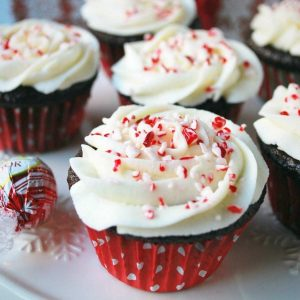 chocolate cupcakes in red polka dot cupcake liners with white frosting topped with crushed peppermint candies