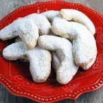 powdered sugar cookies on a red plate