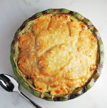 potato gratin baked in a pie plate with a spoon for serving