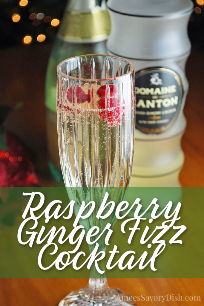 champagne glass containing a raspberry ginger fizz cocktail with bottles in background