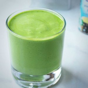 green smoothie in a shortball glass with a can of pineapple juice in the background