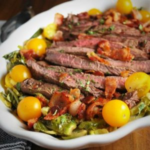 close up of steak salad in a white serving bowl garnished with yellow cherry tomatoes and chopped bacon
