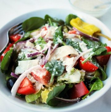 close up of an Italian garden salad in a white bowl with a fork