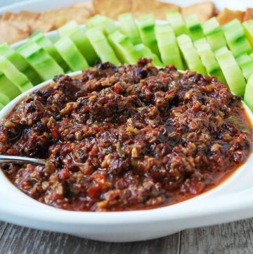 olive tapenade in a bowl with sliced cucumbers and crackers