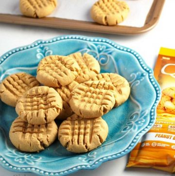 peanut butter cookies on a blue plate with a packet of protein powder next to it