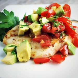 grilled halibut filet topped with avocado relish with a sprig of fresh parsley on the side
