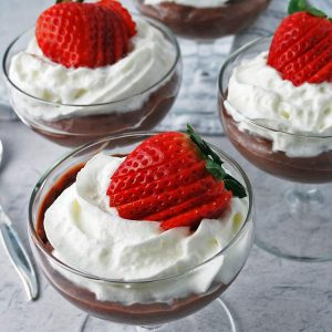 chocolate pudding topped with whipped cream and a sliced strawberry in parfait glasses