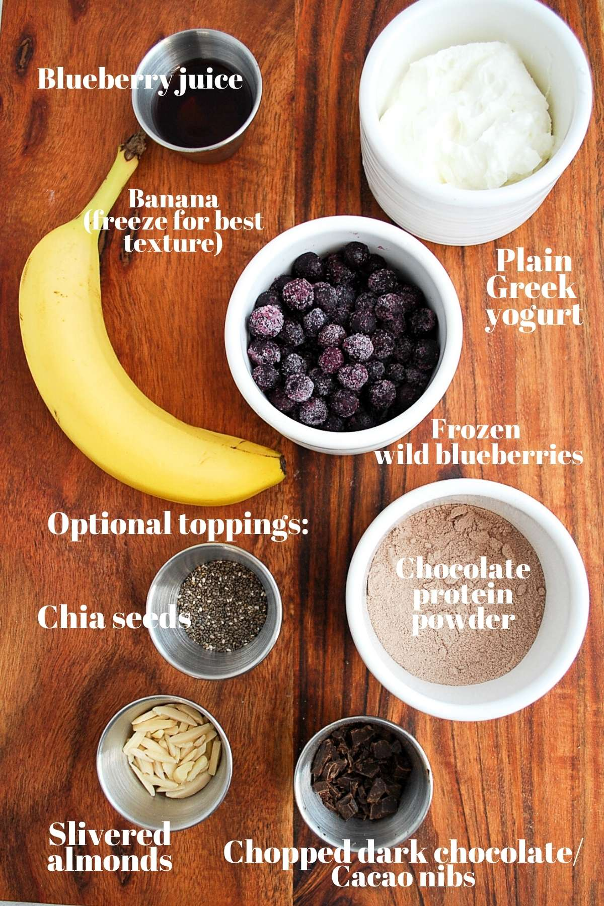 banana, frozen blueberries, yogurt, blueberry juice, chocolate protein powder, chia seeds, almonds, and chopped chocolate for a smoothie bowl