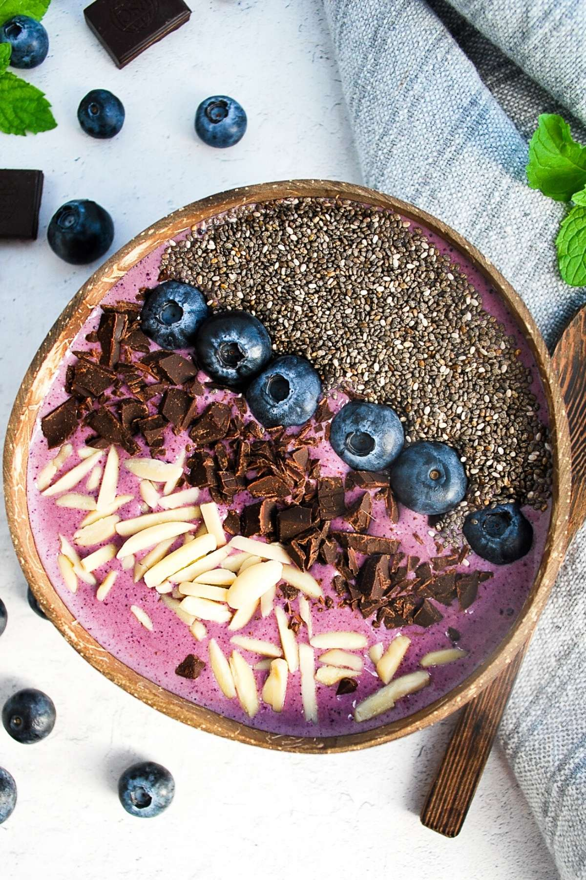 overhead photo of a blueberry smoothie bowl in a coconut shell with blueberries, mint, and chocolate in the background
