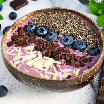 close up of a blueberry smoothie bowl topped with almonds, chocolate, blueberries, and chia seeds