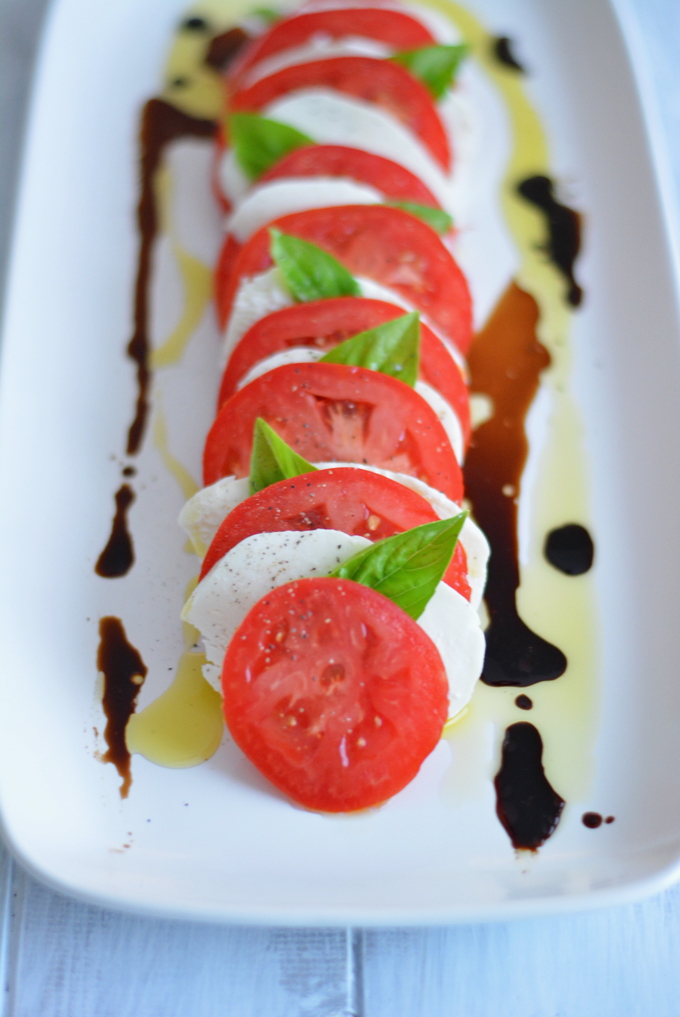 Caprese salad on a platter with balsamic vinegar drizzled down the sides