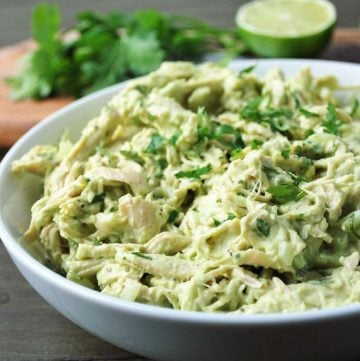 close up of a bowl of avocado chicken salad with fresh lime and cilantro in the background