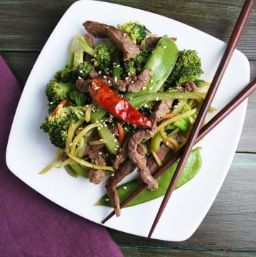 overhead photo of stir fry on plate with hot pepper and chopsticks