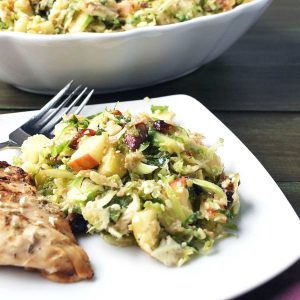 Brussels sprouts salad on a white plate with a grilled chicken breast and a fork