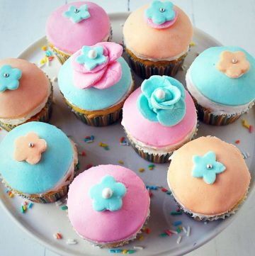 platter of pastel fondant cupcakes with fondant flowers on top