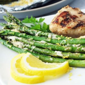 grilled asparagus on a white plate with grilled chicken and lemon