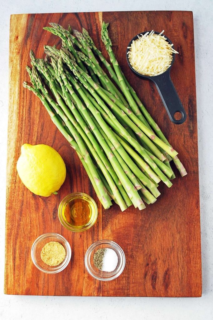 ingredients for grilled parmesan asparagus on a cutting board