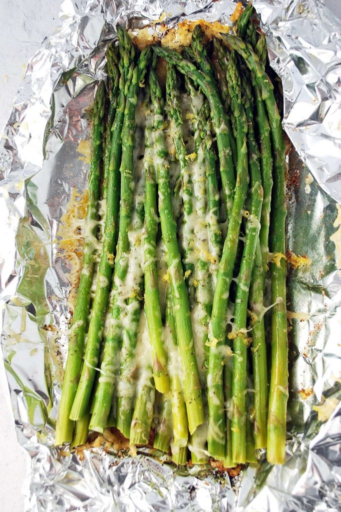 grilled asparagus cooked in a foil packet with melted cheese and lemon zest on top