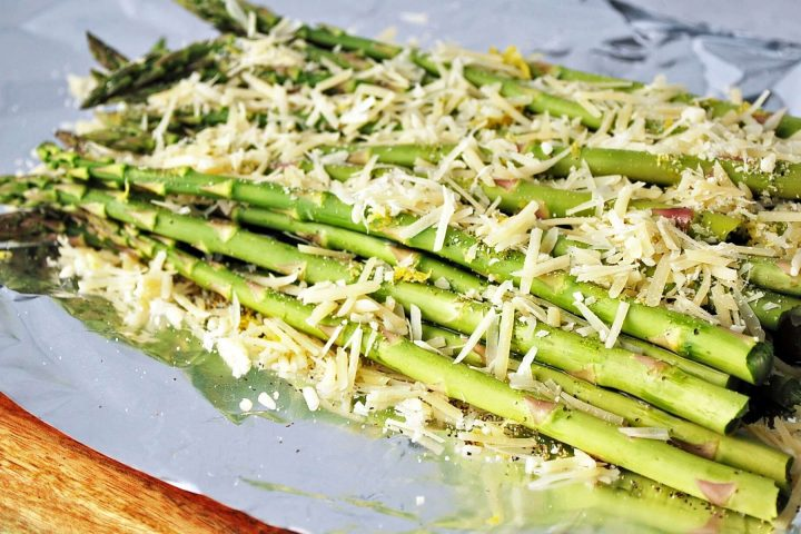 fresh asparagus on foil sprinkled with cheese, olive oil, and lemon zest